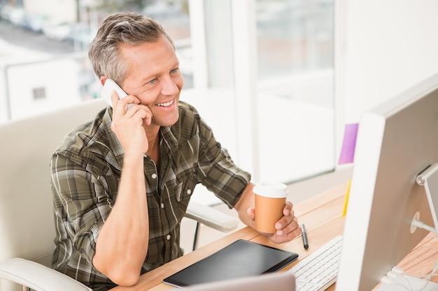 Uśmiechnięty przypadkowy biznesmen ma rozmowę telefonicza