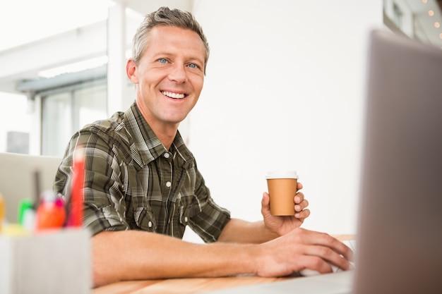 Uśmiechnięty przypadkowy biznesmen pracuje kawę i ma