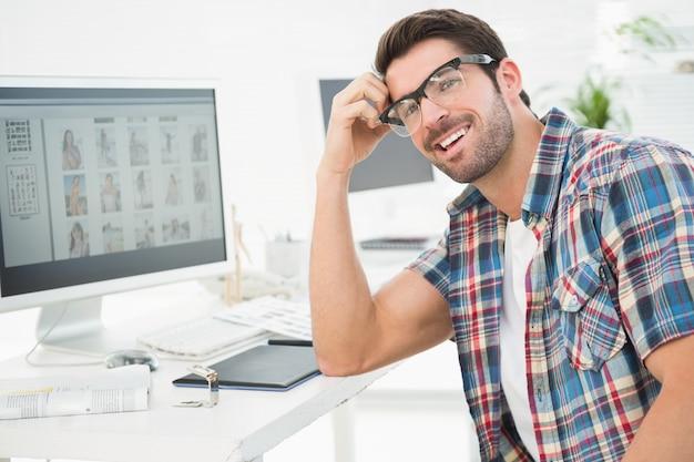 Uśmiechnięty przypadkowy biznesmena obsiadanie przy biurkiem