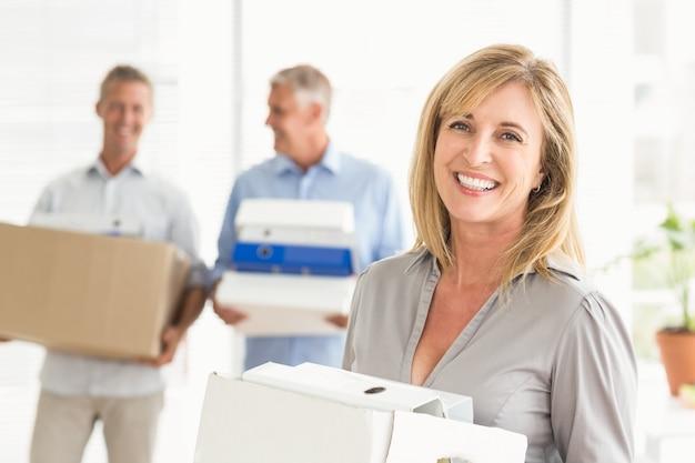 Uśmiechnięty przypadkowy bizneswoman z kartonem