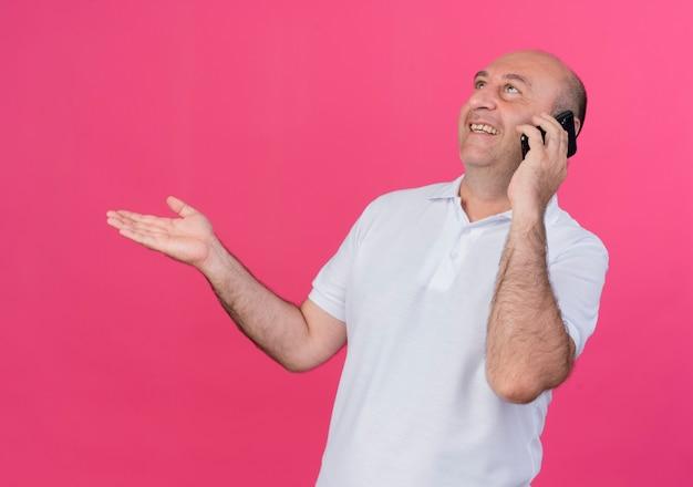 Uśmiechnięty przypadkowy dojrzały biznesmen rozmawia telefon patrząc w górę i pokazując pustą rękę na białym tle na różowym tle