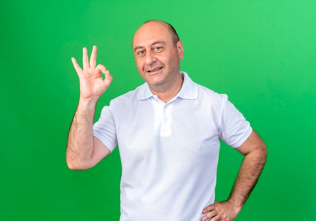 Uśmiechnięty przypadkowy dojrzały mężczyzna pokazuje okey gest i kładzie rękę na biodrze na białym tle na zielonej ścianie