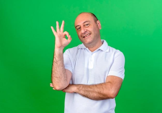 Uśmiechnięty przypadkowy dojrzały mężczyzna pokazuje okey gest na białym tle na zielonej ścianie