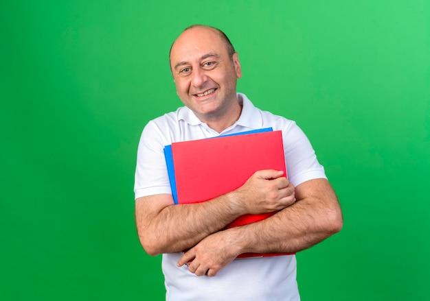 Uśmiechnięty przypadkowy dojrzały mężczyzna trzyma foldery na białym tle na zielonej ścianie