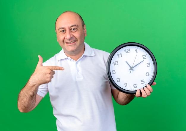 Uśmiechnięty przypadkowy dojrzały mężczyzna trzyma i wskazuje na zegar ścienny na białym tle na zielonej ścianie