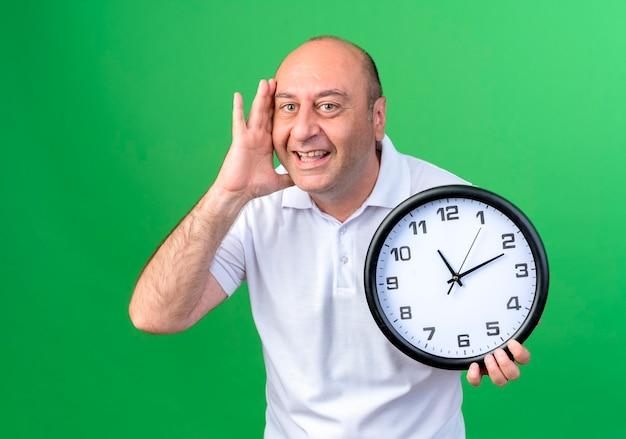 Uśmiechnięty przypadkowy dojrzały mężczyzna trzyma zegar ścienny i kładzie rękę na policzku na białym tle na zielonej ścianie