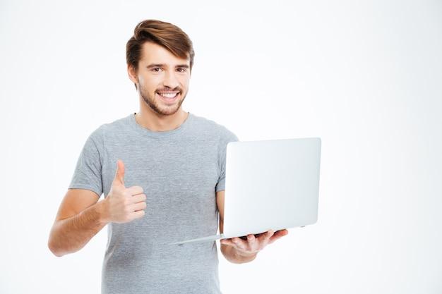 Uśmiechnięty przypadkowy mężczyzna trzymający laptopa i pokazujący kciuk na białym tle na białym tle
