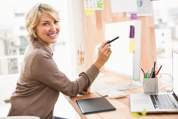 Uśmiechnięty przypadkowy projektant pracuje przy jej biurkiem