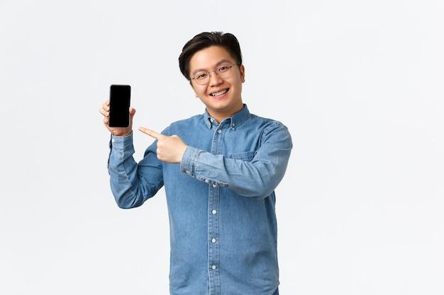Uśmiechnięty przystojny azjata z szelkami i okularami, wskazując palcem na ekran smartfona, mężczyzna pokazujący ...