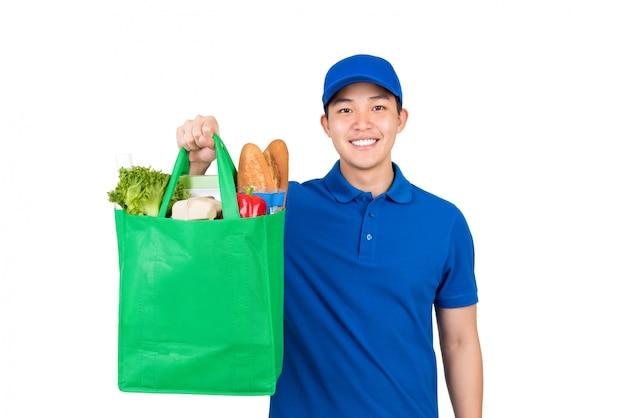 Uśmiechnięty przystojny azjatycki doręczeniowego mężczyzna mienia sklepu spożywczego torba na zakupy odizolowywający na białym tle