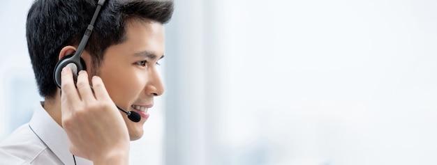 Uśmiechnięty przystojny azjatycki mężczyzna jest ubranym hełmofony pracuje w centrum telefonicznym jako obsługa klienta operator