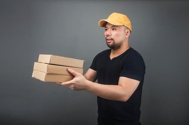 Uśmiechnięty przystojny azjatykci doręczeniowy mężczyzna jest ubranym nakrętkę, daje i niesie pakuneczek, karton, poruszającego domowego dzień i ekspresowej dostawy pojęcie