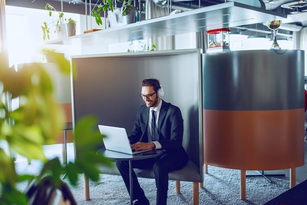 Uśmiechnięty przystojny biznesmen kaukaski brodaty w garniturze, z okularami i słuchawkami, siedząc w miejscu pracy i wpisując na laptopie.