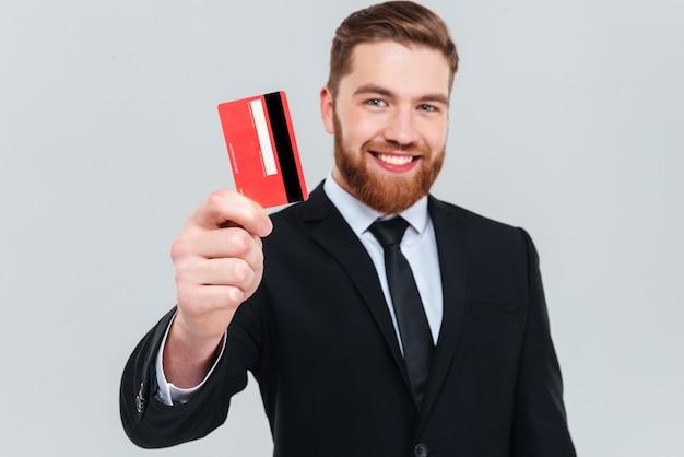 Uśmiechnięty przystojny biznesmen w czarnym garniturze trzymający w ręku kartę kredytową