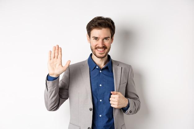 Uśmiechnięty przystojny biznesmen w garniturze macha ręką, wita przyjaciela z przyjazną miną