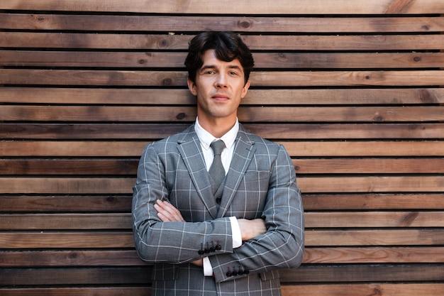 Uśmiechnięty przystojny biznesmen w kostium pozyci z rękami składać