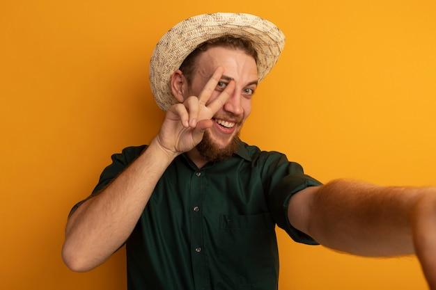 Uśmiechnięty przystojny blondyn w kapeluszu plażowym gestykuluje ręką znak zwycięstwa i udaje, że trzyma przód odizolowany na pomarańczowej ścianie