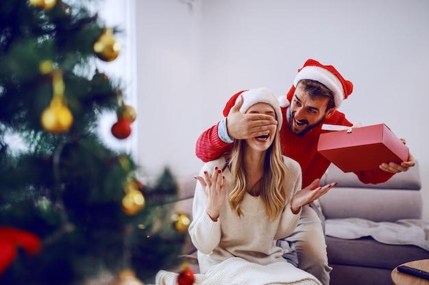 Uśmiechnięty przystojny brodaty kaukaski mężczyzna zakrywa oczy swojej dziewczyny i trzyma prezent. kobieta siedząca na kanapie. obie mają czapki mikołaja na głowach. wnętrze salonu.