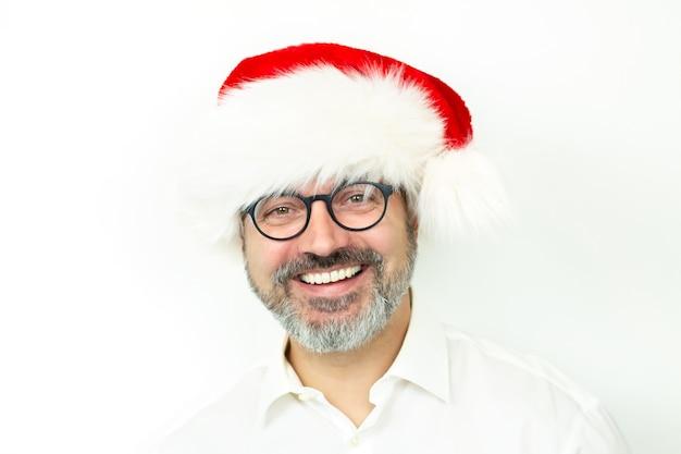 Uśmiechnięty przystojny brodaty mężczyzna ubrany w boże narodzenie kapelusz i okulary