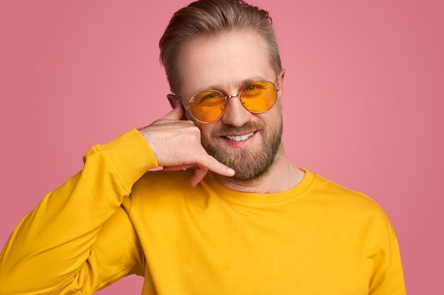 """Uśmiechnięty przystojny brodaty mężczyzna w żółtej bluzie i modnych okularach przeciwsłonecznych, patrzący w kamerę i wykonujący gest """"zadzwoń do mnie"""" na różowym tle"""