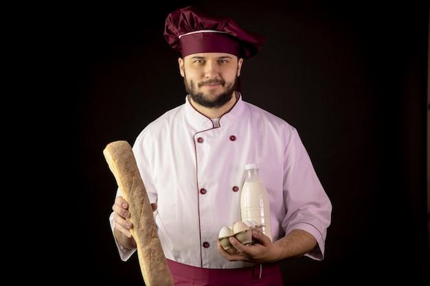 Uśmiechnięty przystojny brodaty szefa kuchni mężczyzna w mundurze trzyma bagietkę, butelkę mleka, jaja