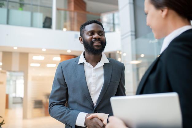 Uśmiechnięty przystojny czarny biznesmen z brodą uzgadnianie partnera biznesowego po zawarciu umowy