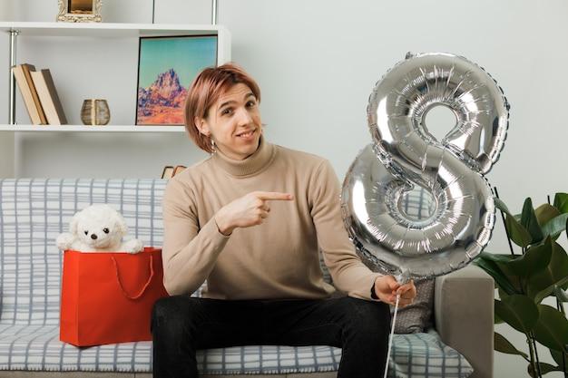 Uśmiechnięty przystojny facet na szczęśliwy dzień kobiet trzyma i wskazuje na balon numer osiem siedzący na kanapie w salonie