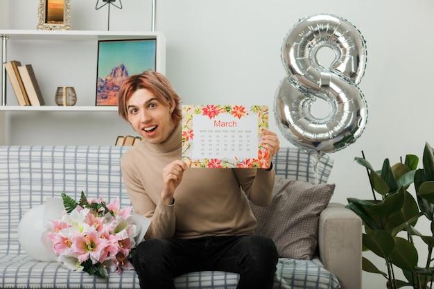 Uśmiechnięty przystojny facet na szczęśliwy dzień kobiet trzymający kalendarz siedzący na kanapie w salonie