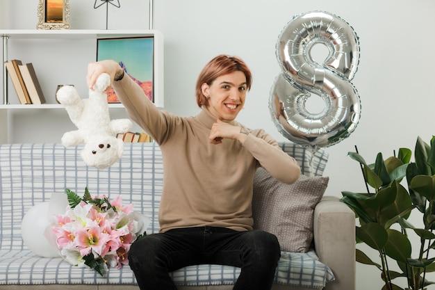 Uśmiechnięty przystojny facet na szczęśliwy dzień kobiet trzymający misia siedzącego na kanapie w salonie