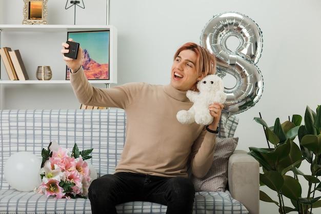 Uśmiechnięty przystojny facet na szczęśliwy dzień kobiet trzymający misia weź selfie siedząc na kanapie w salonie