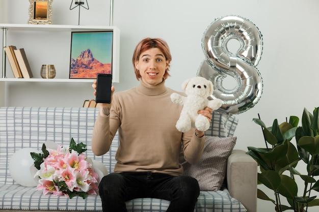 Uśmiechnięty przystojny facet na szczęśliwy dzień kobiet trzymający misia z telefonem siedzącym na kanapie w salonie
