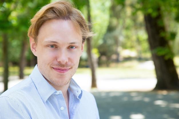 Uśmiechnięty przystojny facet pozuje w parku
