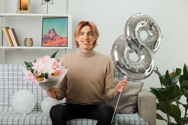 Uśmiechnięty przystojny facet w szczęśliwy dzień kobiet trzymający balon numer osiem i bukiet siedzący na kanapie w salonie