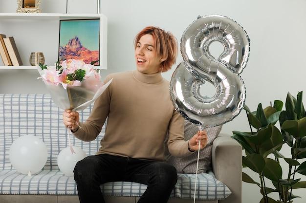 Uśmiechnięty przystojny facet w szczęśliwy dzień kobiet trzymający balon numer osiem i patrzący na bukiet w dłoni, siedzący na kanapie w salonie