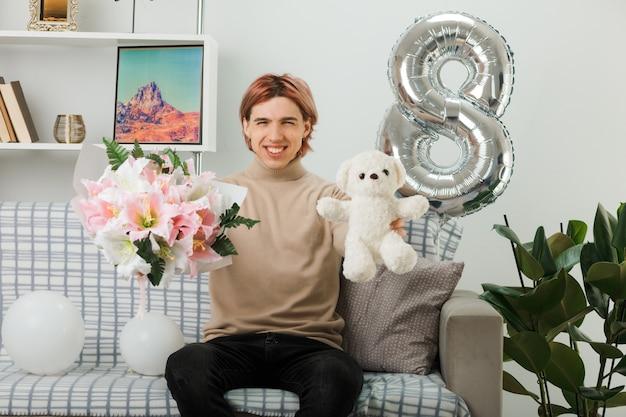 Uśmiechnięty przystojny facet w szczęśliwy dzień kobiet trzymający bukiet z misiem, siedzący na kanapie w salonie