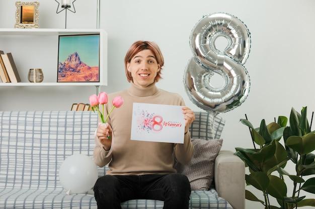 Uśmiechnięty przystojny facet w szczęśliwy dzień kobiet trzymający kwiaty z kartką z życzeniami, siedzący na kanapie w salonie