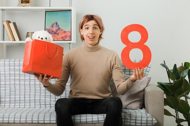 Uśmiechnięty przystojny facet w szczęśliwy dzień kobiet trzymający numer osiem z torbą na prezenty siedzący na kanapie w salonie