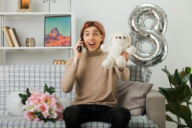 Uśmiechnięty przystojny facet w szczęśliwy dzień kobiet trzymający pluszowego misia, rozmawia przez telefon, siedząc na kanapie w salonie