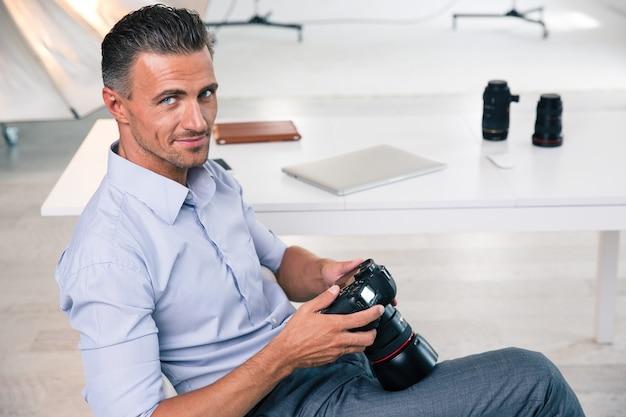 Uśmiechnięty przystojny fotograf używający aparatu w studio