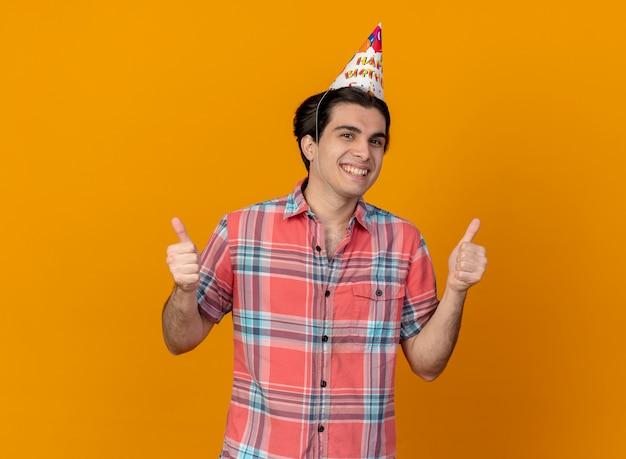Uśmiechnięty przystojny kaukaski mężczyzna noszący kciuki w urodzinowej czapce