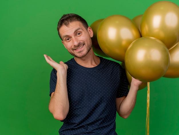 Uśmiechnięty przystojny kaukaski mężczyzna stoi z podniesioną ręką i trzyma balony z helem na białym tle na zielonym tle z miejsca na kopię