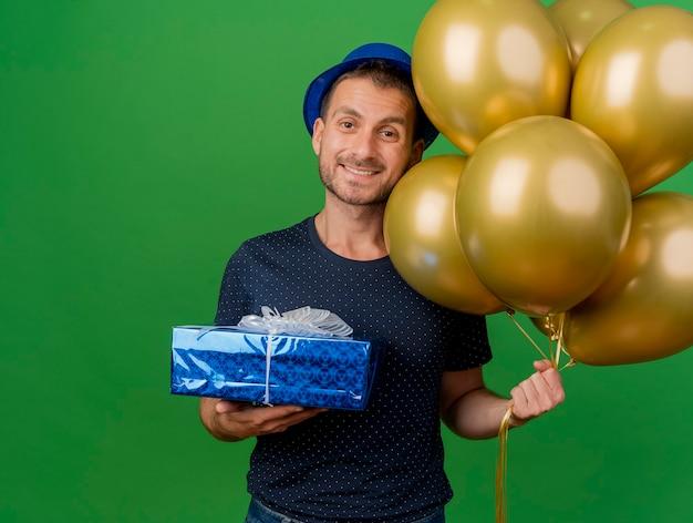 Uśmiechnięty przystojny kaukaski mężczyzna ubrany w kapelusz partii trzyma balony z helem i pudełko na białym tle na zielonym tle z miejsca na kopię