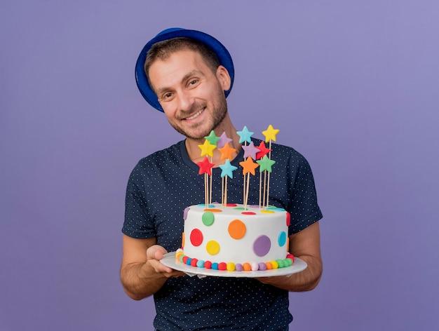 Uśmiechnięty przystojny kaukaski mężczyzna ubrany w niebieski kapelusz trzyma tort urodzinowy na białym tle na fioletowym tle z miejsca na kopię
