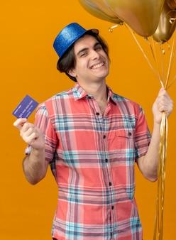 Uśmiechnięty przystojny kaukaski mężczyzna w niebieskiej imprezowej czapce trzyma balony z helem i kartę kredytową, patrząc na kamerę