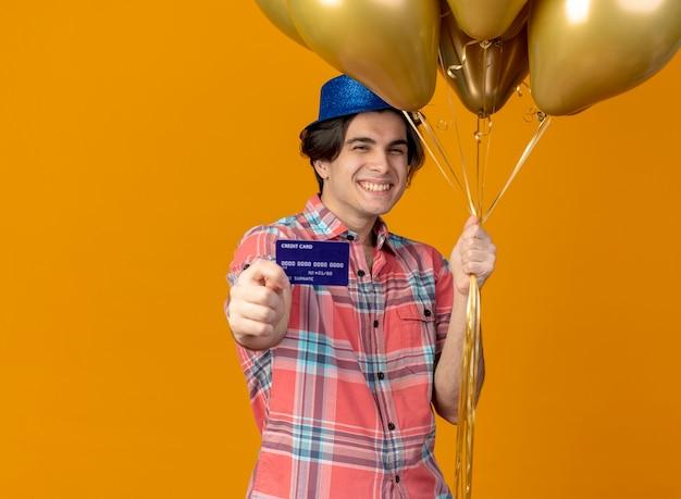 Uśmiechnięty przystojny kaukaski mężczyzna w niebieskiej imprezowej czapce trzyma balony z helem i kartę kredytową