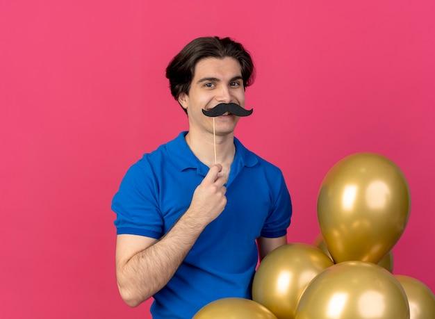Uśmiechnięty przystojny kaukaski mężczyzna w niebieskiej imprezowej czapce trzyma balony z helem i sztuczne wąsy na patyku