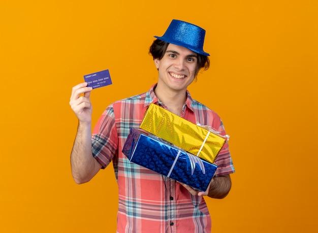 Uśmiechnięty przystojny kaukaski mężczyzna w niebieskiej imprezowej czapce trzyma pudełka na prezenty i kartę kredytową