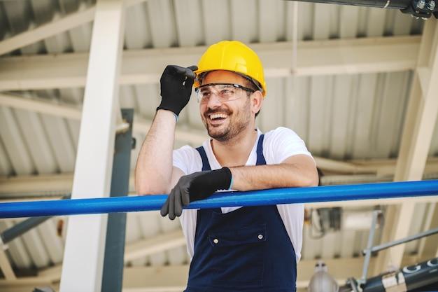 Uśmiechnięty przystojny kaukaski pracownik w kombinezonie iz hełmem na głowie oparty o poręcz. produkcja oleju.