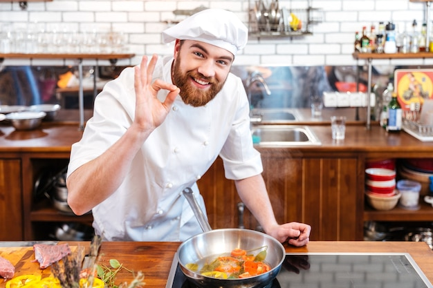 Uśmiechnięty przystojny kucharz przygotowuje jedzenie i pokazuje ok gest w kuchni