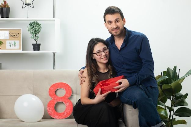 Uśmiechnięty przystojny mężczyzna daje czerwone pudełko ładnej młodej kobiecie w okularach optycznych siedzącej na kanapie w salonie w marcowy międzynarodowy dzień kobiet